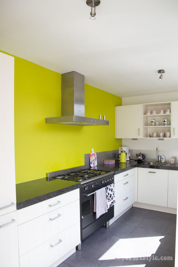 White kitchen with lime green wall | 40plusstyle.com
