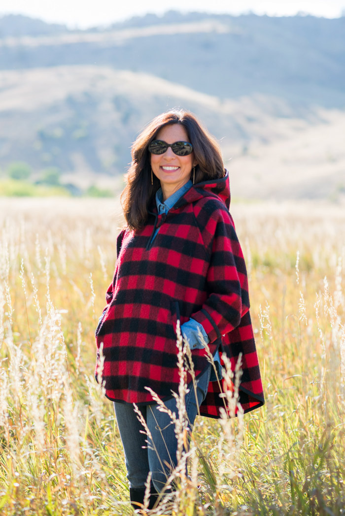 Ana wearing a plaid poncho over polo and jeans | 40plusstyle.com