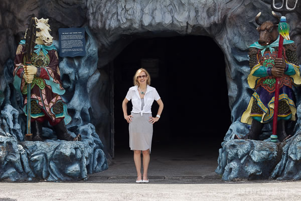 Standing at the entrance of the 10 courts of hell at Haw Par Villa in Singapore | 40plusstyle.com