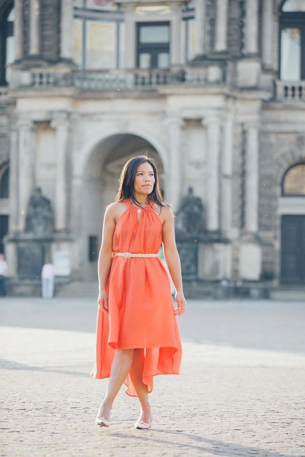 Souri wearing an orange asymmetrical dress | 40plusstyle.com