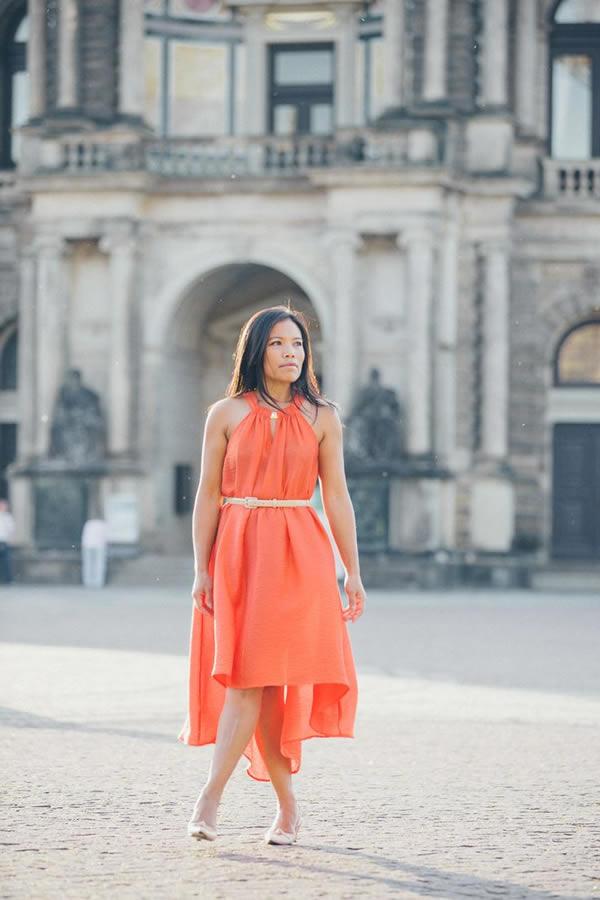 Souri wearing an orange asymmetrical dress | 40plusstyle.com