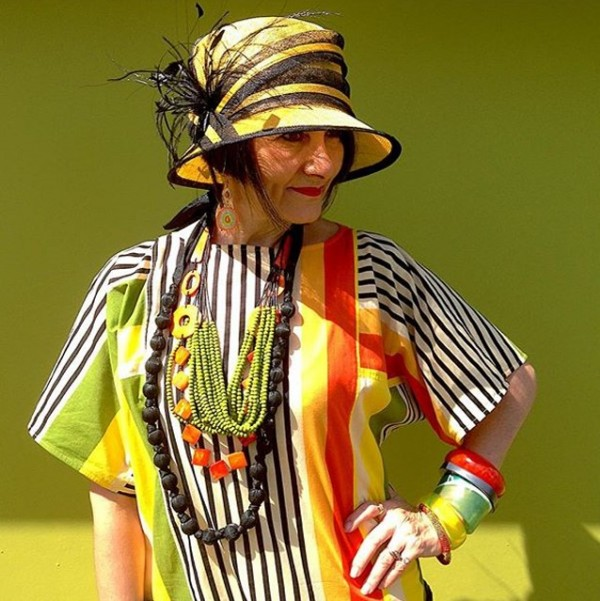 Black, white, orange, yellow, green striped top and feather hat | 40plusstyle.com
