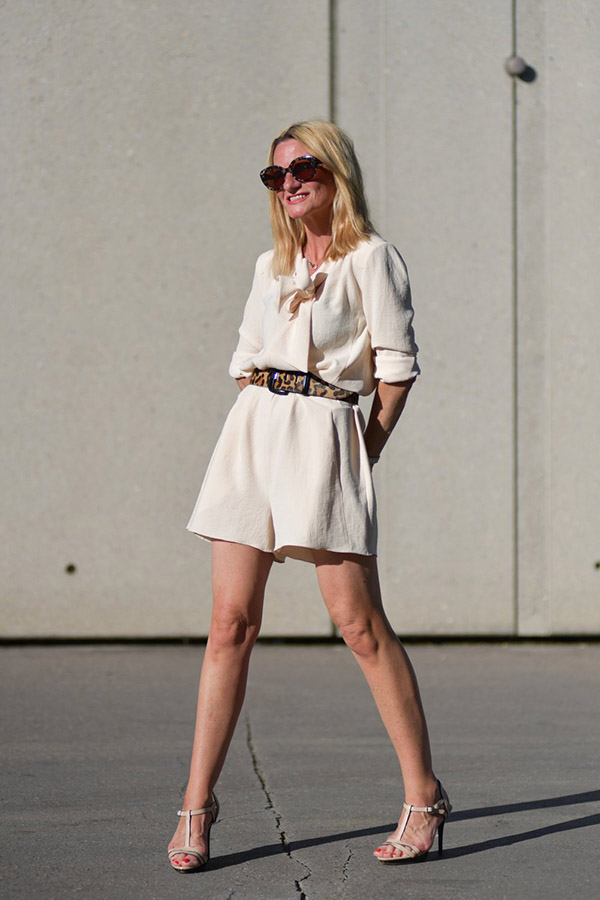 Chic style for women over 40: Beige romper with an animal print belt   40plusstyle.com