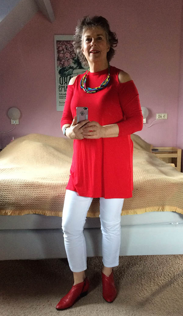 Her chic cold shoulder top in red is nicely paired with simple white pants   40plusstyle.com