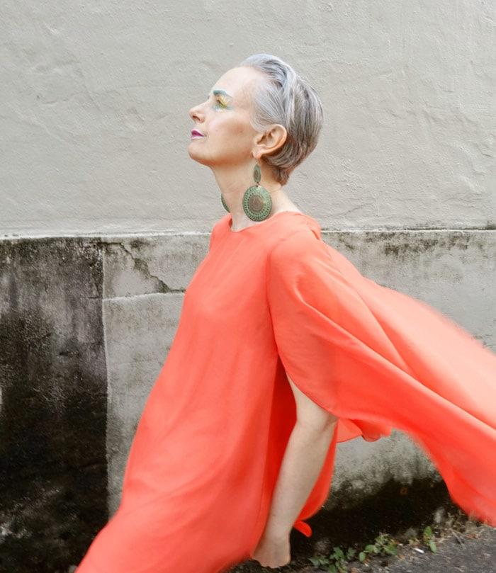 Melanie in an orange dress and statement earrings   40plusstyle.com