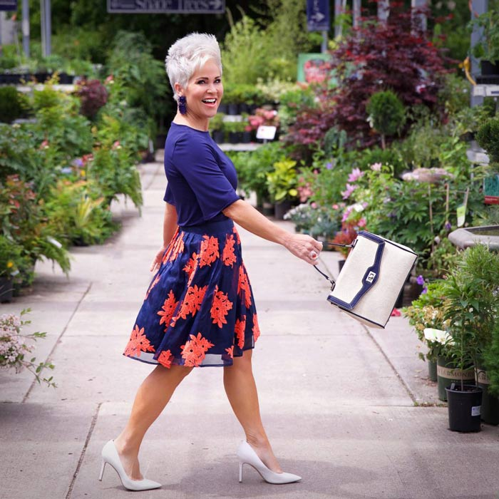 Shauna wearing navy top and floral skirt   40plusstyle.com