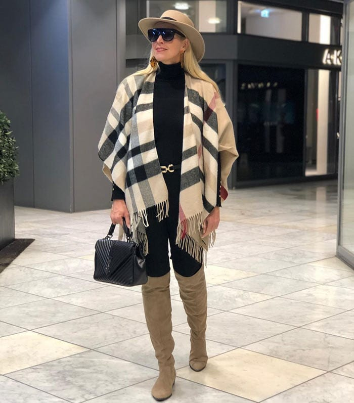 Nadine wearing a knitted ruana over a turtleneck with pants and high boots | 40plusstyle.com