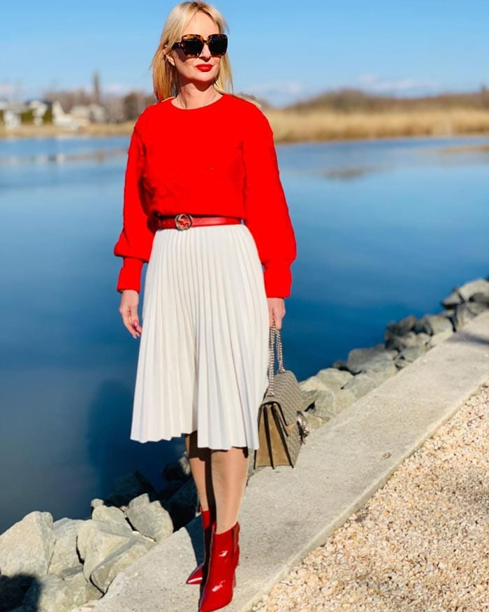 Alice combining a sweater with a pleated skirt   40plusstyle.com