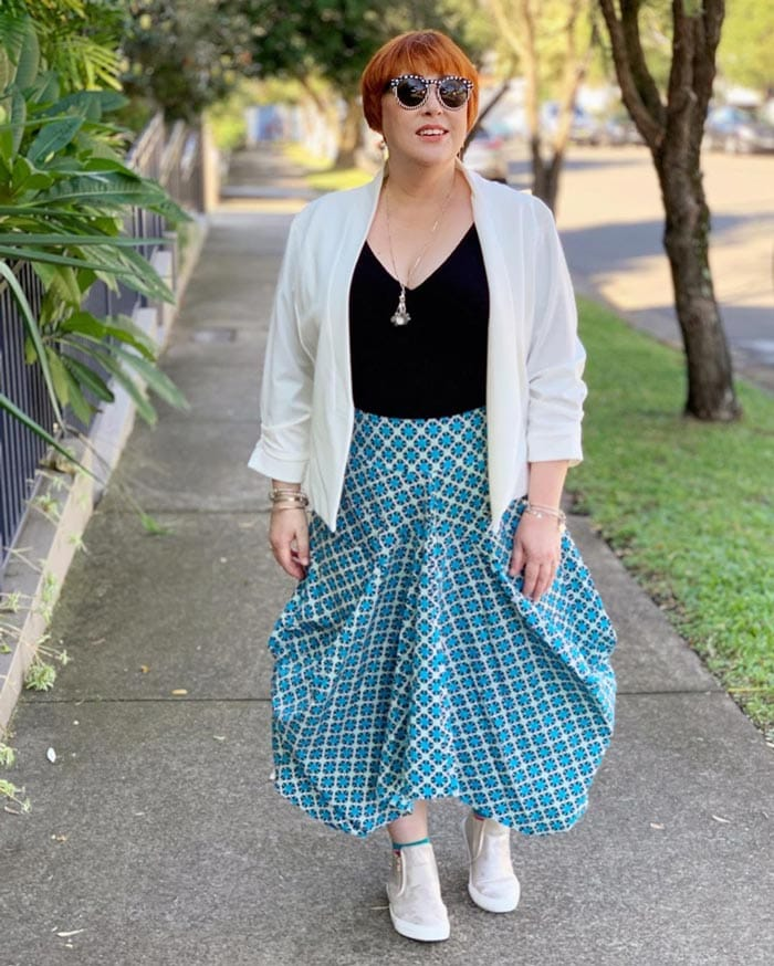 Kim wears a white blazer with her structured skirt   40plusstyle.com