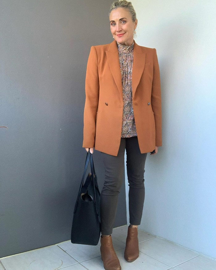 Melinda wears and orange blazer and tan booties for fall | 40plusstyle.com