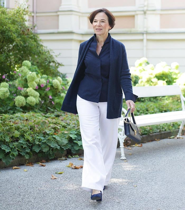 Annette wearing a navy sweater with white pants | 40plusstyle.com