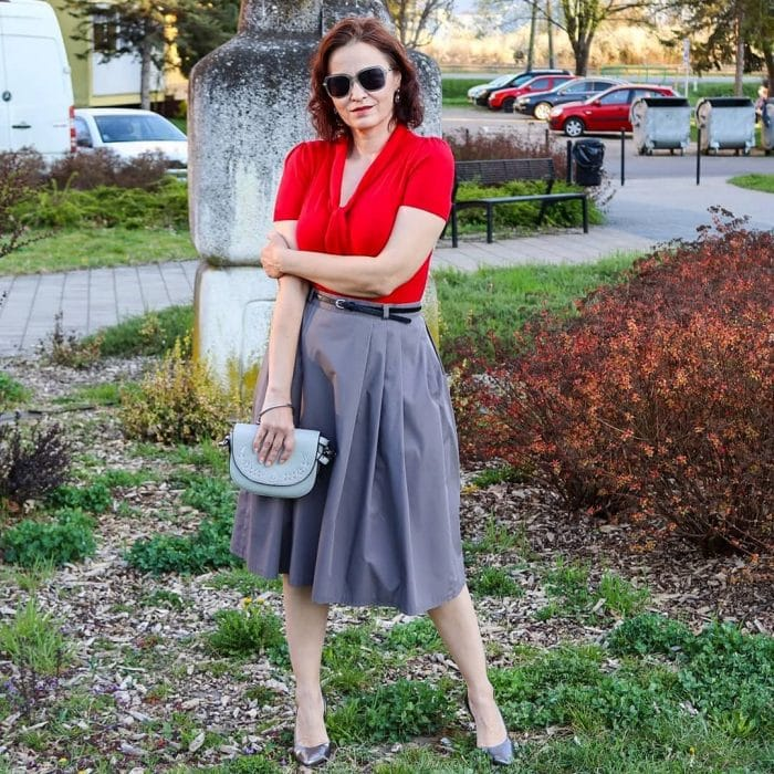 Erika wears a red blouse and gray skirt | 40plusstyle.com