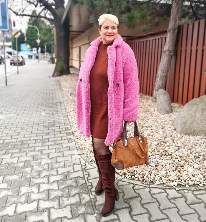 Lucie wears a red sweater dress and pink faux fur coat   40plusstyle.com