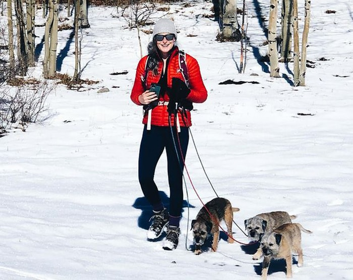 Amanda wears a bright red coat for a walk with her three dogs | 40plusstyle.com