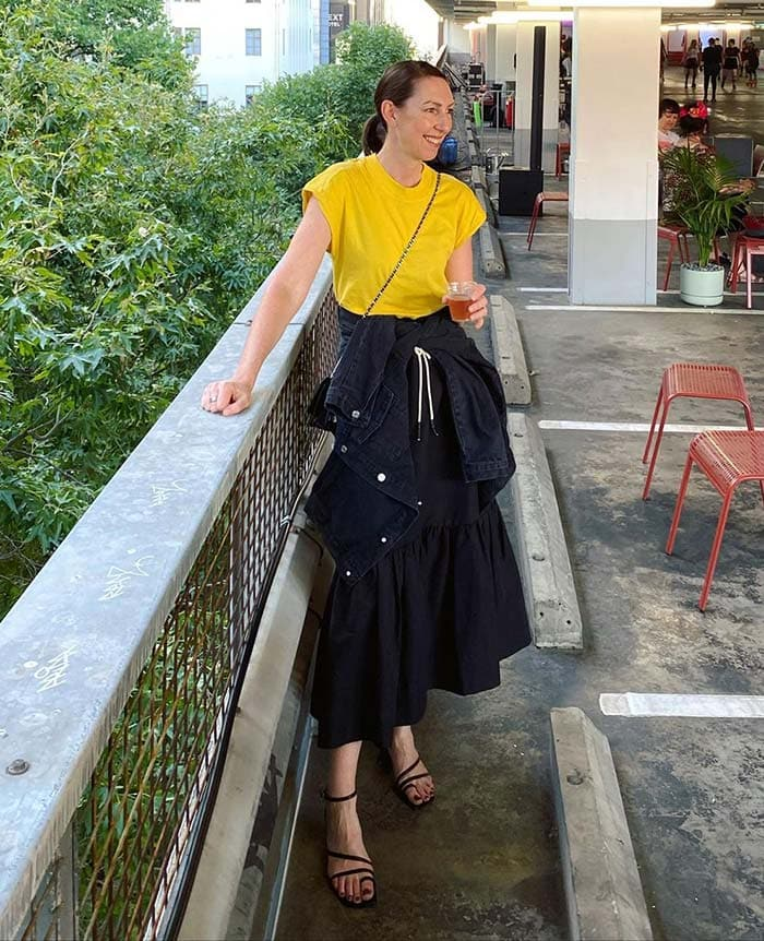 Sally wears a yellow t-shirt and black skirt   40plusstyle.com