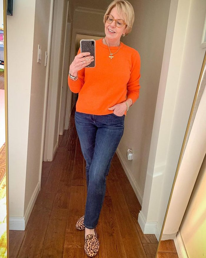 Susan in an orange sweater and jeans   40plusstyle.com