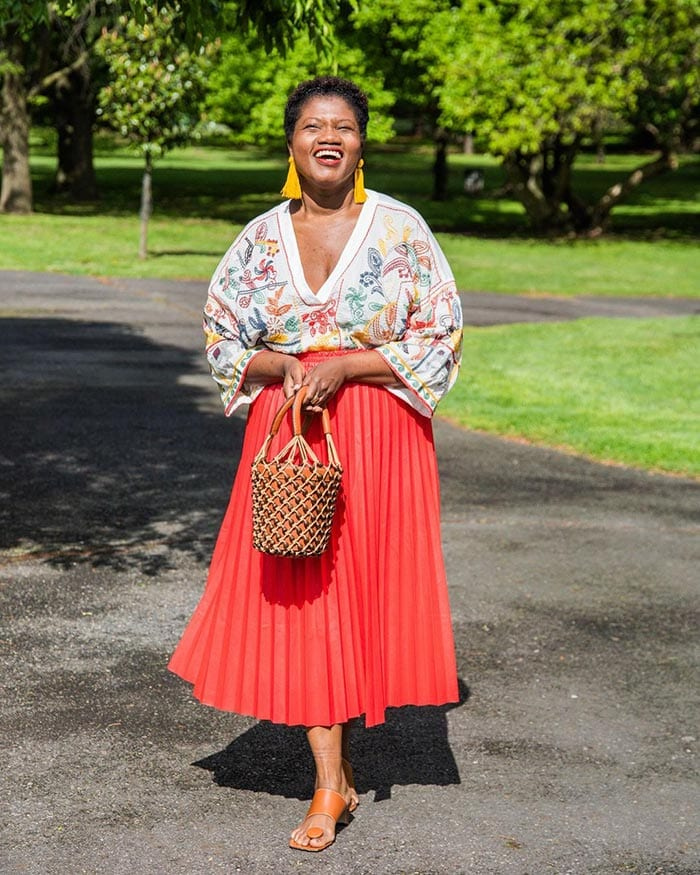 Georgette in embroidered boho top, pleated skirt, sandals and boho accessories | 40plusstyle.com