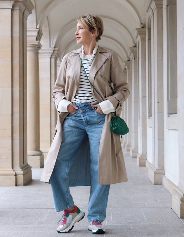 Claudia wears a trench coat and jeans | 40plusstyle.com