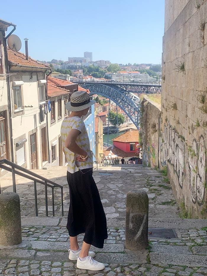 Wearing a black skirt, graphical t-shirt and sneakers in Porto, Portugal   40plusstyle.com