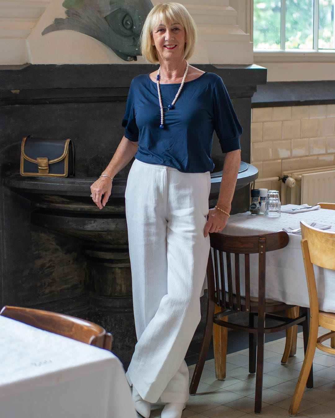 Greetje in wide leg pants and a navy top | 40plusstyle.com